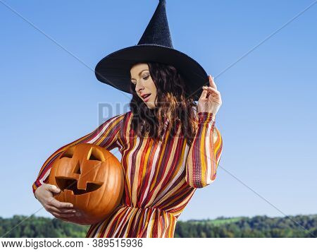 Young Sexy Woman Holding A Carved Pumpkin And Wearing A Witch Hat For Halloween Theme.
