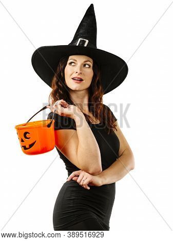 Young Sexy Redhead Woman In Witch Hat And Holding A Pumpkin Candy Bucket For Halloween Theme.
