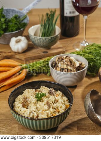Bowl Of Risotto On A Table With Ingredients, Mushrooms, Garlic, Carrots, And A Glass Of Wine.