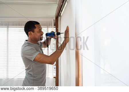 Happy Smiling African American Male Using Electric Drill On The Wall While Covid-19 Quarantine At Ho
