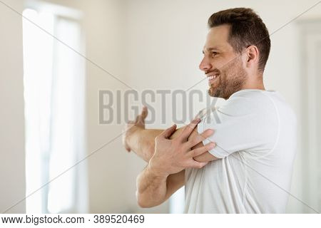 Cheerful Guy Exercising Stretching Arms Training Standing At Home. Morning Physical Exercises, Male