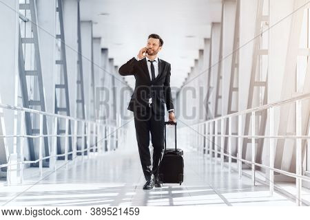Business Trip, Travelling For Work Concept. Wealthy Handsome Entrepreneur With Suitcase Walking By A