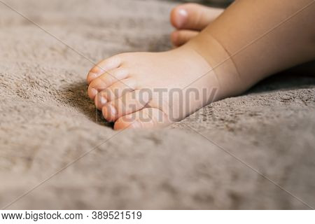Baby Feet On Coverlet. Toes. Horizontal Photo. Close-up.