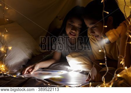 Family Concept. Elder Sister And Sister Reading Book With Flashlight Together Before Bedtime. Sister