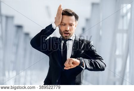 Worried Businessman Looking At His Watch And Touching Head, Running By Airport Terminal, Empty Space