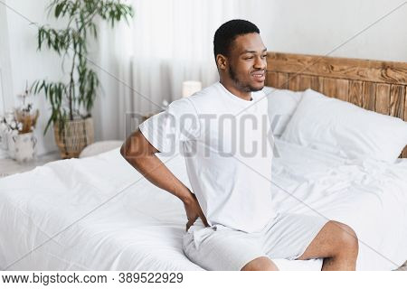 Backache Pain. African American Man Touching Aching Back Suffering From Ache Sitting In Bed At Home.