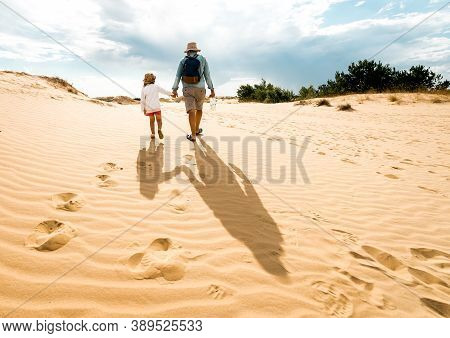 Father With Daughter In The Desert. Beautiful Texture Of Desert Sand Dunes In Oleshky Sands, Kherson