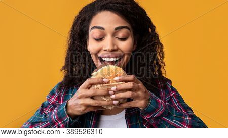 Junk Food. Closeup Portrait Of Hungry African American Woman Eating Tasty Burger. Funny Woman Holdin
