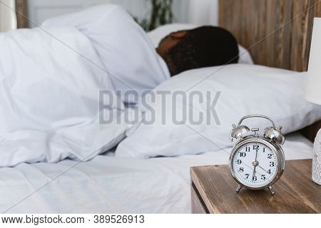 Oversleeping. Overslept Black Man Sleeping Through Alarm Clock In The Morning Lying In Bed At Home,