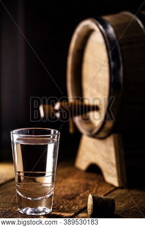 Glass Of Distilled Alcohol, Such As Rum, Cachaça Or Cognac, With An Oak Barrel In The Background.