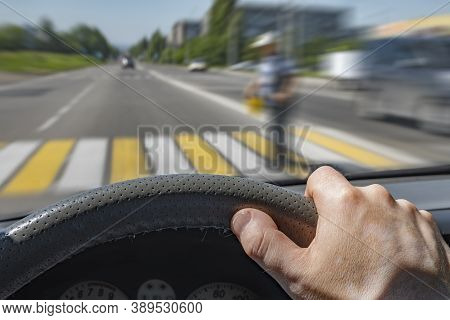 The Driver Hand On The Steering Wheel Of A Car Moving At High Speed And Passing A Pedestrian Crossin
