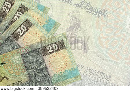 20 Egyptian Pounds Bills Lies In Stack On Background Of Big Semi-transparent Banknote. Abstract Busi