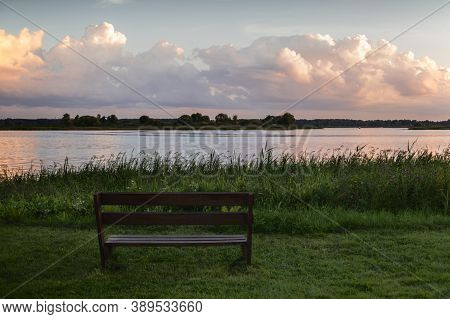 Bench By The Lake At Sunset Overlooking Beautiful Clouds On A Summer Evening