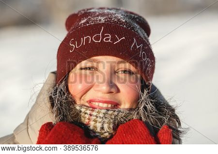 Happy Young Woman In Red Winter Hat On The Snow Sunny Day Against Blue Sky