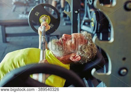Pushing The Limits Of Human Body. Side View Of A Mature Caucasian Man Lifting Weighted Bar Or Barbel