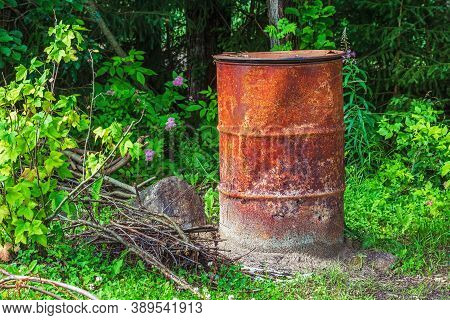 Old Rusty Iron Barrel Used To Incinerate Garbage In A Suburban Garden Plot.