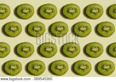 Kiwi Pattern. Repetition Of A Round Kiwi Wedge On A Light Yellow Background. Top View Of Green Kiwi
