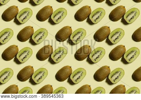 Kiwi Pattern. Repetition Of Kiwi Halves On A Light Yellow Background. Top View Of Green And Brown Ki