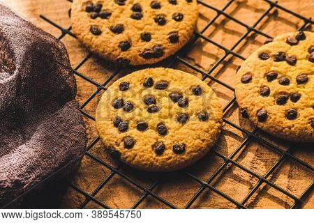 Delicious Fresh Chocolate Chip Cookies With Chocolate On A Cooling Rack On Wooden Background, Close