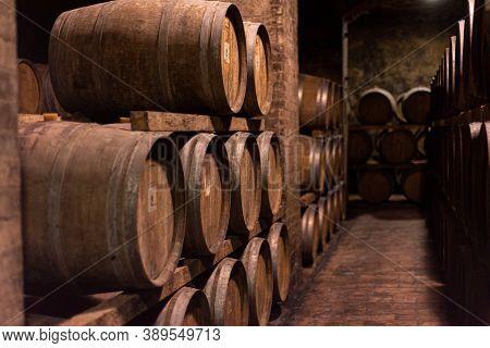 Wooden Barrels For Wine Aging In The Cellar. Italian Wine.