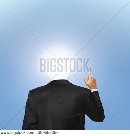Business Concept. Man In Black Suit Hold One Finger Up With The Enlightened Bulb Instead Of His Head