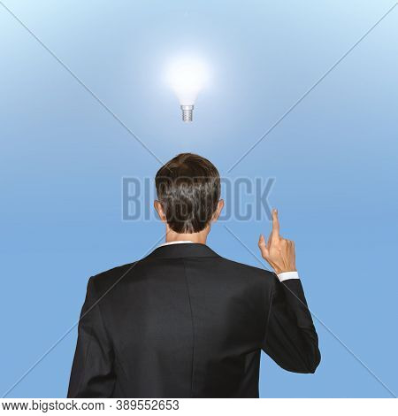 Business Concept. Man In Black Suit Hold One Finger Up With The Enlightened Bulb Over His Head Symbo