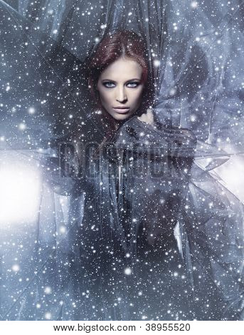 Fashion shoot of young attractive woman in blowing silk over the snowy background