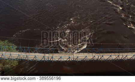 Suspended Footbridge Across The River. Suspended Wooden Pedestrian Bridge Across The River. Bridge I