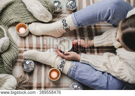 Young Woman Sits On Plaid In Cozy Knitted Woolen White Sweater And Socks Holds Cup Of Cocoa In Her H
