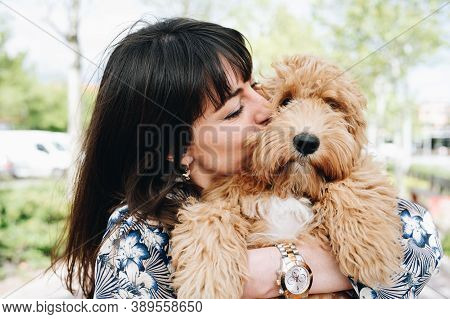 Attractive Woman Kisses And Hugs Her Lovely Puppy. Love For Animal Concept.