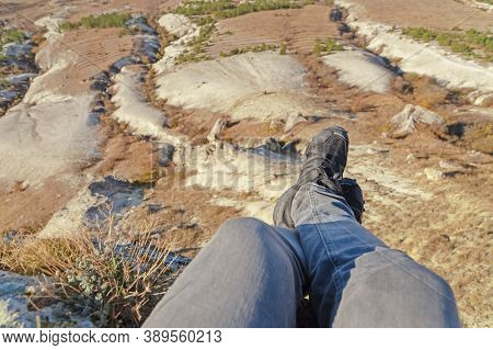 Man Sits On The Edge Of Mountain Cliff With His Legs Dangling Over Precipice In The Distance Steppe