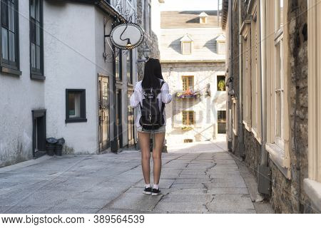 A Chinese Woman Walking Down A Narrow Alleyway Near The Place Paris In The Old Port Area Of Quebec C