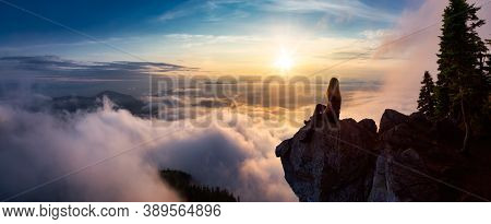 Female Hiker On Top Of A Mountain Covered In Clouds. Magical Colorful Sunset. Taken On Top Of St Mar
