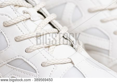 Pair Of White Sneakers With Shoelaces Closeup. New White Sneakers And White Shoelaces In Closeup.