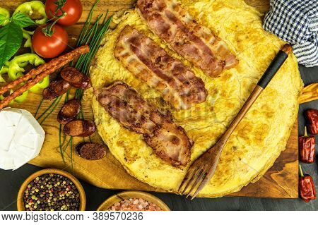 Egg Omelette With Bacon And Sausage. Omelette With Tomatoes,  Green Onion On Wooden Plate. Frittata
