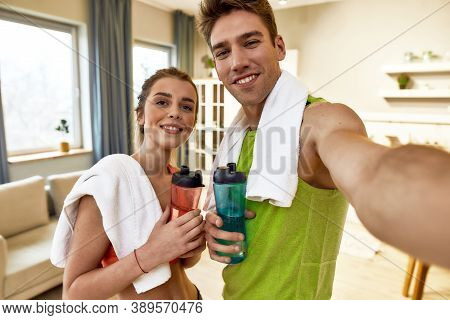 Young Couple In Sportswear Smiling, While Taking A Selfie, Showing Healthy Lifestyle After Exercisin