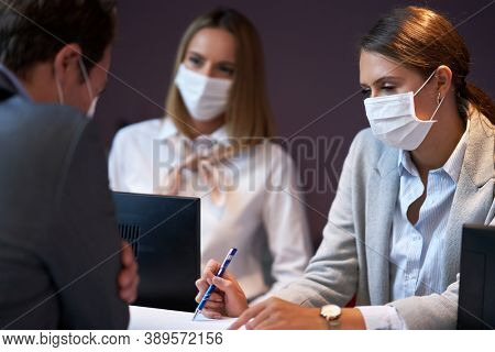 Businessman in mask at the reception desk of a hotel checking in