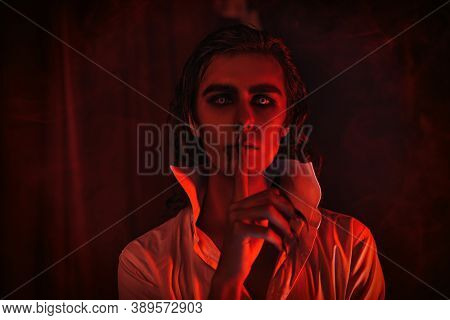 Portrait of a handsome wary vampire freezing in place, showing the need for silence with a hand gesture in the red light. Traditional vampire.  Halloween.