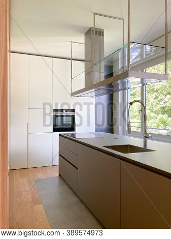 Modern kitchen with suspended hood, large sink, oven and wooden worktop. Design apartment. Nobody inside
