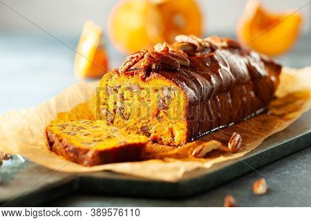Delicious pumpkin pecan and raisin cake on cutting board. Loaf of pumpkin bread.