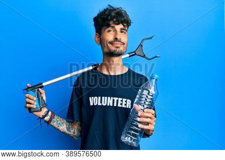 Young hispanic man holding plastic bottle and litter picker to recycle smiling looking to the side and staring away thinking.