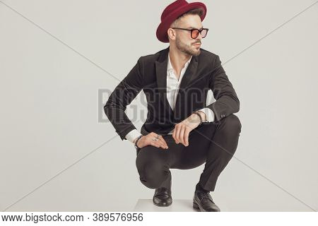 Pensive fashion model looking away, wearing sunglasses and hat while crouching on gray studio background