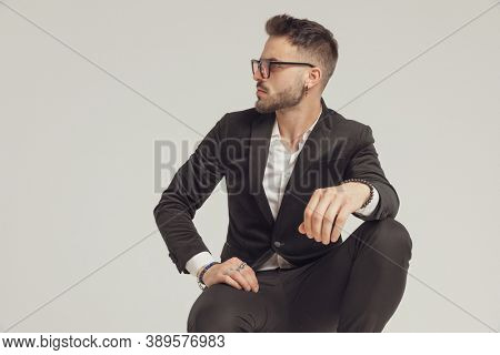 Confident fashion model curiously looking away and wearing sunglasses while crouching on gray studio background