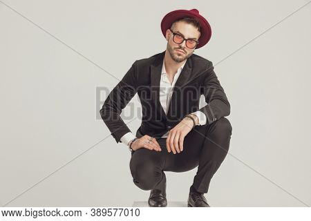 Upset fashion model looking forward, wearing sunglasses and hat while crouching on gray studio background