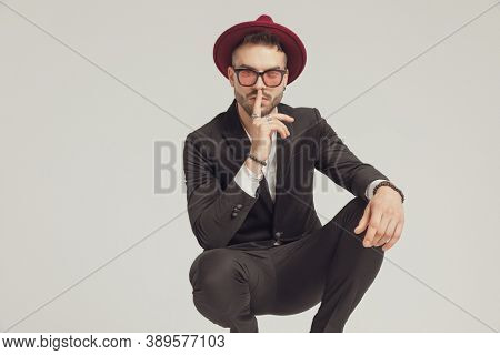 Mysterious fashion model gesturing being quiet, wearing sunglasses and hat while crouching on gray studio background