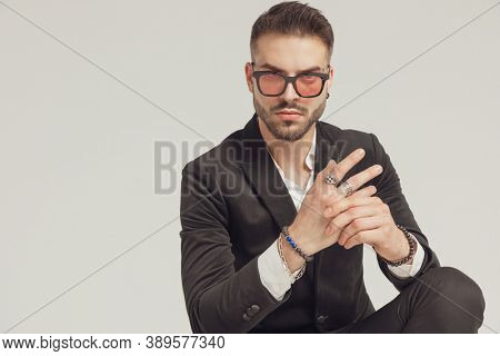 Serious fashion model adjusting his rings, wearing sunglasses while crouching on gray studio background