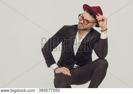 Pensive fashion model fixing his hat and looking away, wearing sunglasses while crouching on gray studio background
