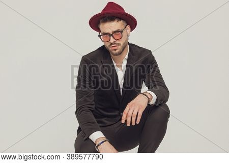 Confident fashion model wearing sunglasses and hat while crouching on gray studio background