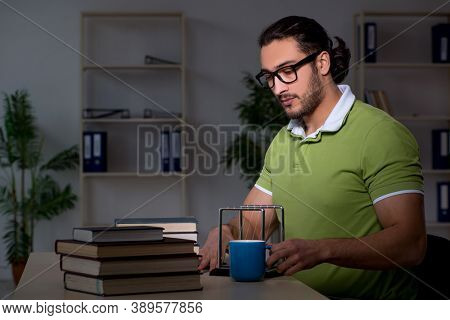 Young male student physicist working hard at night time