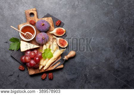 Antipasto plate with cheese, figs and grapes. Appetizer board. Top view with copy space